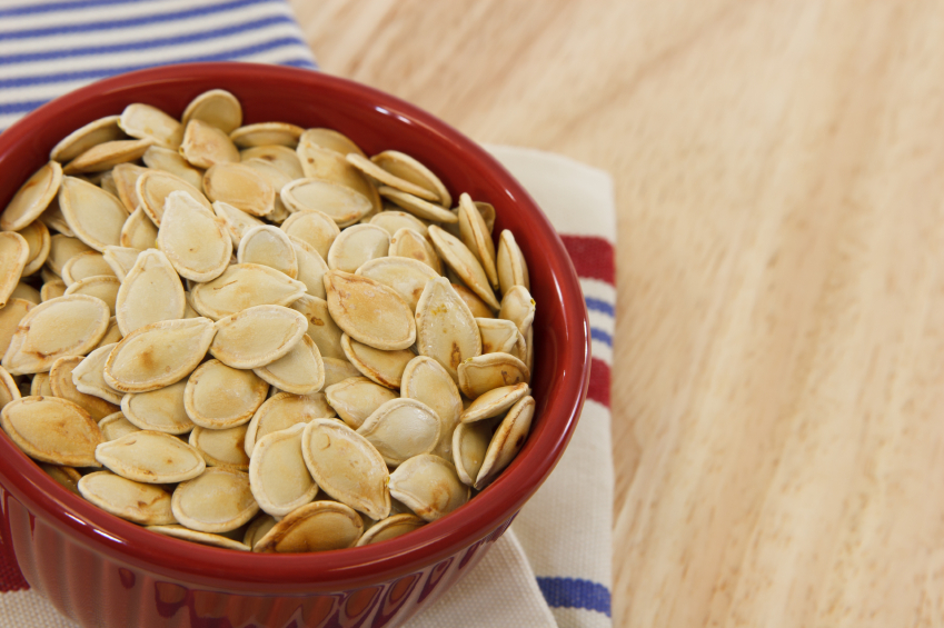 Healthy pumpkin seeds in a red bowl set against a red, white and blue towel make a healthy snack option