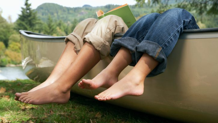 Barefoot boy and girl (4-10 years) reading in canoe by lake, low section