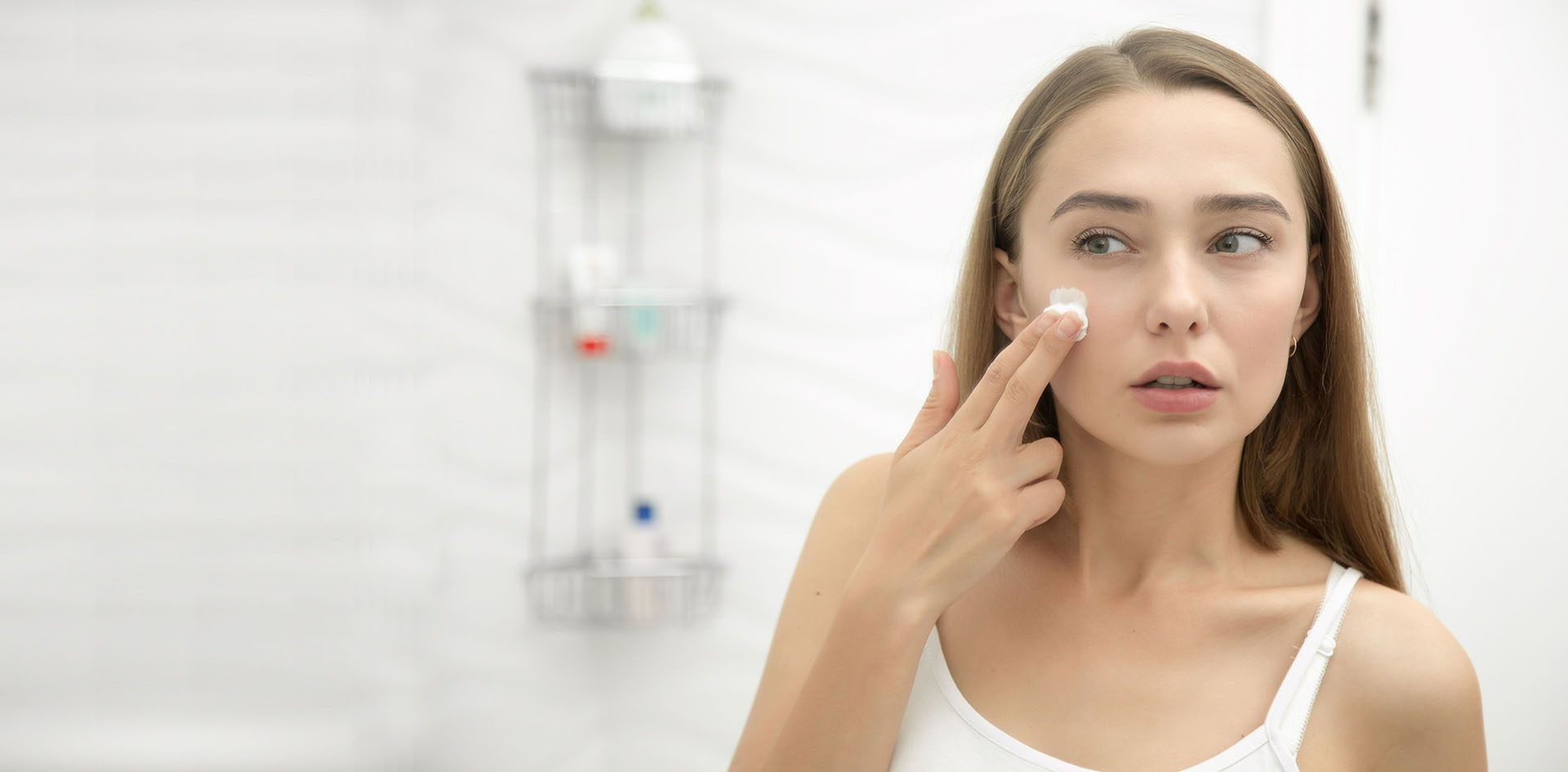 Young beautiful woman applying cream to face in the bathroom